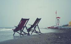 Два пляжных кресла на берегу.