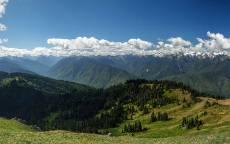 Синее небо, белые облака, зеленые холмы, лес