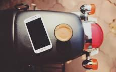 Чашка с кофе и смартфон лежат на сиденье мопеда