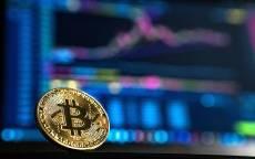 Монета биткоин на фоне биржевого графика