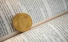 Монета биткоин на страницах книги