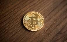 Монета биткоин лежит на деревянном столе