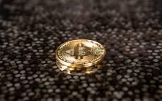 Монета биткоин лежит на стеклянном столе