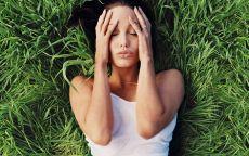 Анджелина Джоли лежит в зеленой траве.
