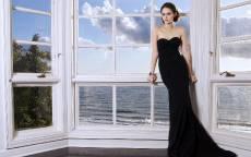 Американская актриса Уилла Джоанна Ченс Холланд в черном платье стоит у окна с видом на море