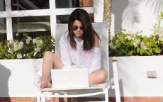 Молодая актриса Селена Гомес сидит в белом кресле за ноутбуком