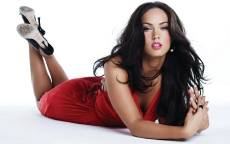 Актриса Меган Фокс в красном платье лежит на белом полу