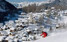 Лыжник на фоне зимней деревушки