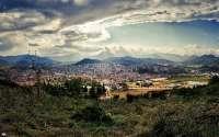 Испания, панорама города в горах, солнце в облаках