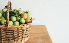 Корзина, деревянный стол, зеленые яблоки